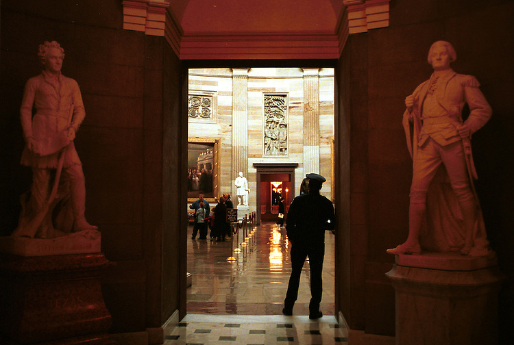 capitolguard2/121002 - A police officer stands watch over tourists in the Captiol rotunda.