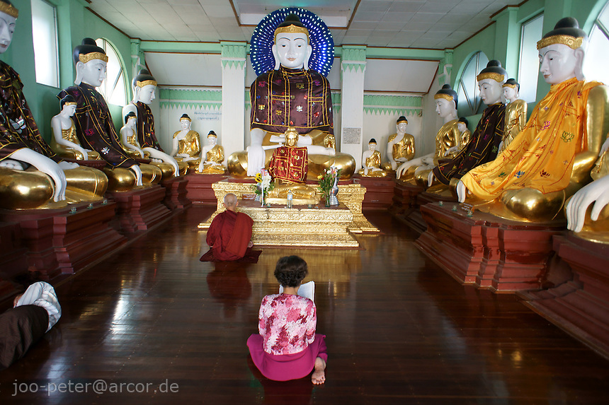 worshipper praying in buddha temple on Shwedagon pagoda complex, Yangon, Myanmar, 2011