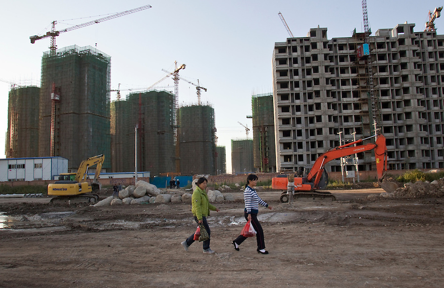Two women walk through a construction site of high rise apartments in Dagang, in Tianjin.