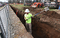 NWA Democrat-Gazette/J.T. WAMPLER  Phillip Mason of Hindsville works Monday March 26, 2018 digging a trench behind the retaining wall along Arkansas Ave. in front of Old Main at the University of Arkansas in Fayetteville. The trench is part of a drainage system being put in behind the wall to prevent erosion damage.