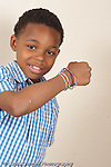 8 year old boy portrrait showng wrist with silly bands colored shaped rubber bands collection vertical