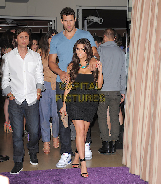 Kris Humphries & Kim Kardashian .The Noon by Noor launch event at At the Sunset Tower in West Hollywood, California, USA..July 20th, 2011         .full length blue t-shirt black strapless dress skirt top circles fiance fiancee engaged couple tall short tall short jeans denim hands arms on shoulders.CAP/RKE/DVS.©DVS/RockinExposures/Capital Pictures.