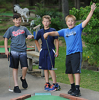 NWA Democrat-Gazette/ANDY SHUPE<br /> Bryson Whitmill (from left), 10; and Dalton Whitmill, 9; watch as friend Connor Brannan, 11, celebrates a hole-in-one Wednesday, June 14, 2017, while playing miniature golf at Gator Golf in Fayetteville. The three are fifth-, fourth- and sixth-graders respectively in West Fork and are attending the annual West Fork Summer Camp this week which is meant for students up to sixth grade.