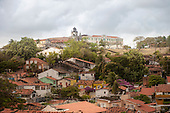 Olinda, Pernambuco State, Brazil. Overview of colonial rooftops with a baroque church on top of the hill.