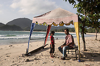 "Indonesia – Sumatra – Aceh – Lampuuk – Sabri Rahman, 34 years old sits under the shade of a small gazebo with his daughter on the beach where he owns a bar.  Sabri was on the porch of his house when the wave carried him several km away. Hours later when the water receded and Rahman came back to a scene of utter devastation, he started to frantically look for his family. The then 24-year-old guy volunteered to gather, pile up and bury hundreds of bodies, but was not able to find any member of his family, because most of the bodies had been pushed km away. Rahman lost 22 relatives, including his parents and six of his siblings. His 9-year-old brother was the only other survivor. ""It was extremely difficult to deal with my feelings"" he explains. Although his kids helped him deal with the pain, "" I still have to keep myself busy in order not to think about it"" he says, fondly caressing his daughter Sasqia."