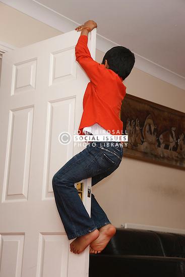 Boy climbing up door in living room.