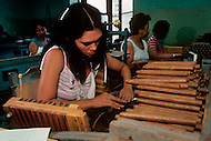 Cuba, March 1992: Torcedores (cigar rollers) , rolling cigars in La Corona, The largest cigar factory in Havana. In 1966, Fidel Castro decided that women should enter into the aristrocracy of the Torcedores. A Torcedor in his life learns how to roll one to maximum of three different size of cigars. The fastest Torcedores can roll upto 110 cigars per day.