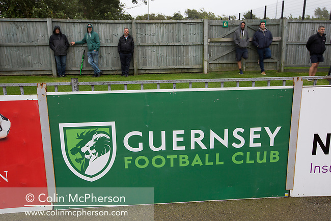 Fans watching the first-half action as Guernsey take on Corinthian-Casuals in a Isthmian League Division One South match at Footes Lane. Formed in 2011, Guernsey FC are a community club located in St. Peter Port on the island of Guernsey and were promoted to the Isthmian League Division One South in 2013. The visitors from Kingston upon Thames won the fixture by 1-0, watched by a crowd of 614 spectators.