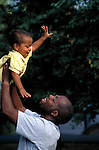 father holding up laughing toddler son