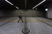 A Japanese male office worker walks through an underpass in Shinjuku, Tokyo, Japan. Tuesday November 29th 2016