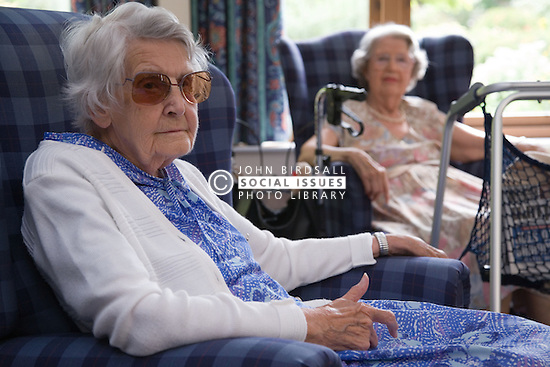 Two older ladies resting in the communal lounge of a residential nursing home,