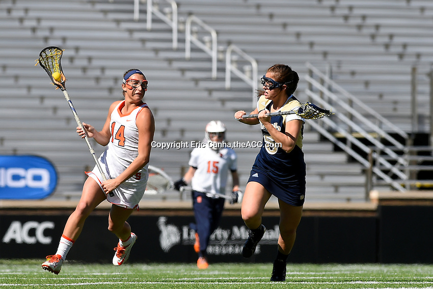 Syracuse's Kasey Mock (14) and Notre Dame's Rachel Sexton (5) battle at midfield during the 2014 ACC Women's Lacrosse Quarterfinals in Boston, MA, Thursday, April 24, 2014. (Photo by Eric Canha,<br /> theACC.com)