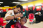 Kent the Barber gives Elijah Wiley, 6, a haircut at Graffitis SWAG Shop in South Atlanta, Georgia, July 25, 2013. The shop gives Hot Wheels cars to boys after their haircuts as a prize.