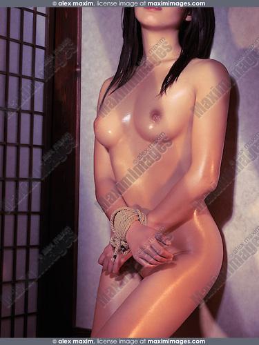 Beautiful naked asian woman standing at a wall with tied hands. Bondage Shibari art nude photo.