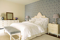 The boldly patterned wallpapered wall behind the bed adds colour and dramatic effect to the otherwise neutral bedroom