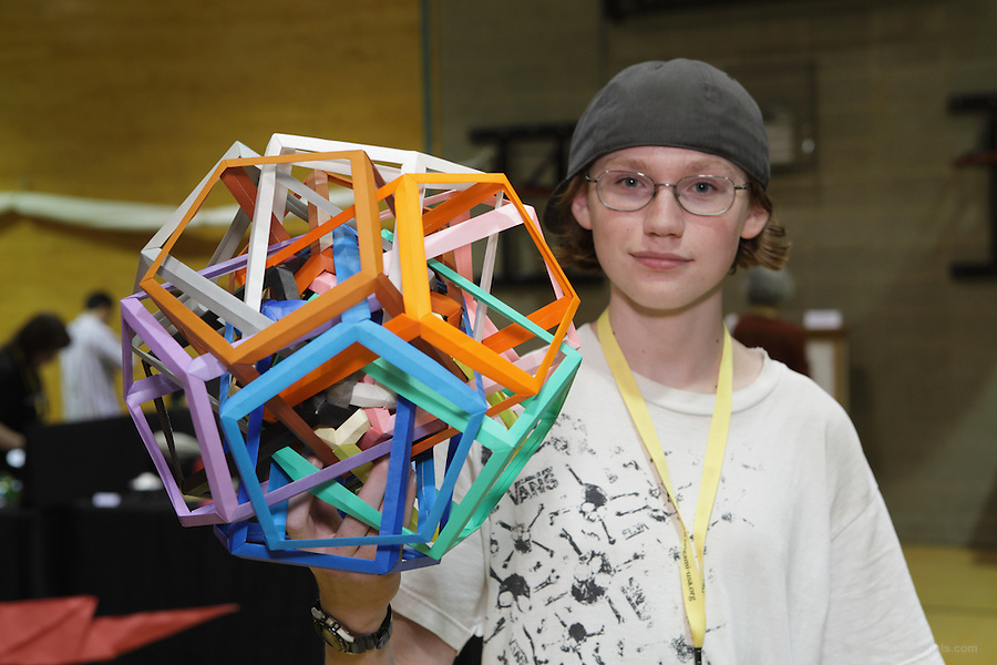 New York, NY, USA - June 22, 2012: Byriah Loper, an Origami designer from Kentucky holds a colorful modular creation at the OrigamiUSA 2012 convention exhibition held at Fashion Institute of Technology in New York City.