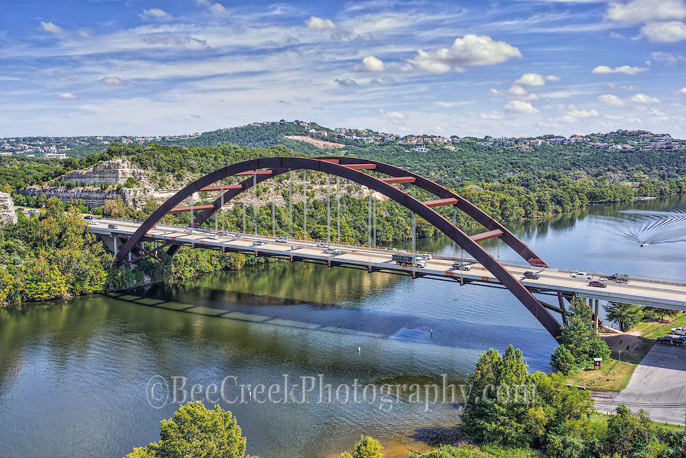 A little different aerial view of the Austin 360 Bridge view over Lake Austin.  This was an aerial capture of the Pennybacker Bridge as we were doing a job for a client in this area so we had permission to photograph from here.  Great day with nice blue sky and good clouds.  Only one lone boat on the water so you can see the reflections in the water, beecreekphoto.com, Tod GrubbsWe were able to capture this high quality aerial image because we use a full frame camera on our drone for out still photographs so we can get the best image which can be printed easlity as a 40 x 60 or larger size without loss of resolution.​
