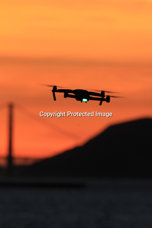 A drone flies during a sunset over the Golden Gate Bridge seen from the east-bay shore line.