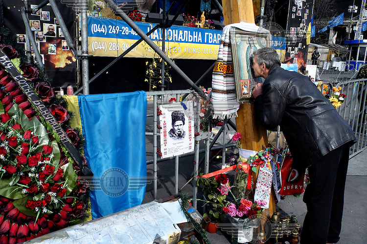 A man kisses a picture, attached to a wooden cross, of the Virgin Mary that forms a part of a memorial to those killed in Kiev during anti-government protests. On 21 November 2013 protests against the government of President Viktor Yanukovych were sparked by the Ukrainian government's decision to suspend preparations for the signing of an association agreement with the European Union that would have increased trade with the EU. Some believe that the U-turn came about as a result of pressure from President Putin of Russia who wants Ukraine to join a customs union with itself, Kazakhstan and Belarus. Russia offered 15 billion dollars of soft loans and reduced price gas to Ukraine at the same time as discussions with the EU were taking place. After weeks of protests and a number of deaths, Prime Minister Mykola Azarov and the entire cabinet resigned. On 18 February, after Yanukovych's party scuppered a move to change the constitution to reduce the powers of the president, renewed fighting between protesters and police broke out and had cost the lives of around 80 people by Friday 21st February. By 22 February Yanukovych had fled Kiev. In the days following the Ukrainian parliament decided to strip him of the presidency.
