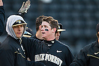 Conor Keniry (14) of the Wake Forest Demon Deacons is greeted by teammates after scoring a run against the Georgetown Hoyas at Wake Forest Baseball Park on February 16, 2014 in Winston-Salem, North Carolina.  The Demon Deacons defeated the Hoyas 3-2.  (Brian Westerholt/Four Seam Images)