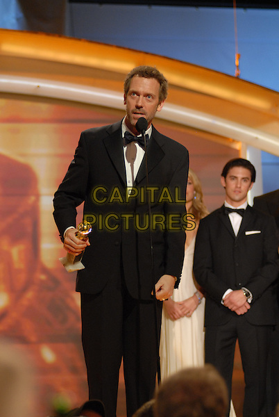 "HUGH LAURIE.Accepts his award for Best Actor in a Television Series-Drama for his role in ""House"" .Telecast - 64th Annual Golden Globe Awards, Beverly Hills HIlton, Beverly Hills, California, USA..January 15th 2007. .globes half length microphone stage black tuxedo jacket trophy.CAP/AW.Please use accompanying story.Supplied by Capital Pictures.© HFPA"" and ""64th Golden Globe Awards"""
