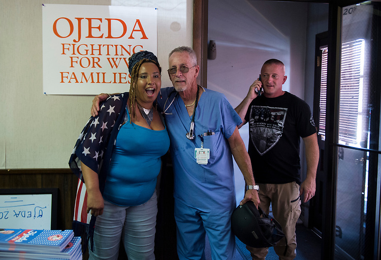 UNITED STATES - July 5: Richard Ojeda, right, talks on the phone as his Field Director Charkera Ervin, 32, hugs his father, Richard N. Ojeda, Sr. inside the campaign headquarters in Logan, West Virginia Thursday July 5, 2018. Ojeda is a first-term lawmaker from southern West Virginia running to represent the state's 3rd Congressional District as a Democrat. (Photo By Sarah Silbiger/CQ Roll Call)