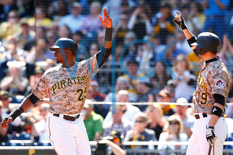 Gregory Polanco #25 and Chris Stewart #19 of the Pittsburgh Pirates react after Polanco scored against the Detroit Tigers during the game at PNC Park in Pittsburgh, Pennsylvania on April 14, 2016. (Photo by Jared Wickerham / DKPS)