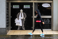 "Pictured: A woman walks by a poster of Sir Philip Green on the door of the now closed down BHS store in Oxford Street, Swansea, Wales, UK. Tuesday 13 September 2016<br /> Re: Former owner of BHS, Sir Philip Green has paid a surprise 'visit' to the closed down BHS store in Swansea.<br /> He was spotted in the doorway of the Oxford Street store, which closed its doors for the last time last month.<br /> In his hand was a BHS shopping bag with money spilling out of it.<br /> Sir Philip had owned BHS before selling it for £1 last year.<br /> He is claimed to have taken millions out of the company in dividends and left behind a £571m pensions deficit.<br /> Alongside the poster are the words: ""Thankyou for your custom Sir""."
