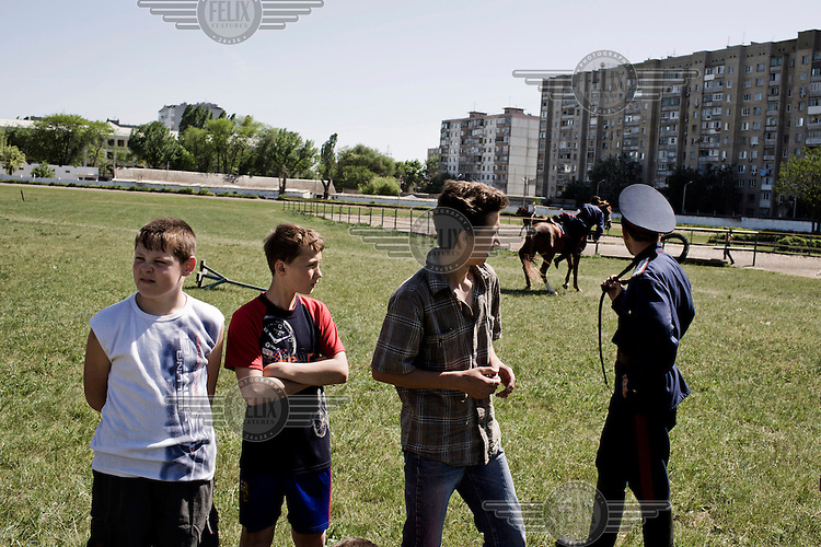 At a Cossack riding stables a group of senior Cossacks from the Don Cossack Army give swordmanship and riding lessons to a group of young boys. In the background a Cossack falls from his horse during the demonstration.