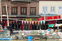 Colorful laundry hanging on lines along the shoreline of Dal Lake, Srinagar, Kashmir, India.