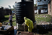 A woman is seen collecting water from a water tank in Nawab Colony, near the deserted Union Carbide factory in Bhopal. The ground water is believed to be contaminated near the site of the deserted Union Carbide factory in Bhopal, India. Twenty-five years after an explosion causing a mass gas leak, in the Union Carbide factory in Bhopal, killed at least eight thousand people, toxic material from the 'biggest industrial disaster in history' continues to affect local Bhopalis. A new generation is growing up sick, disabled and struggling for justice. The effects of the disaster on the health of generations to come, both through genetics, transferred from gas victims to their children and through the ongoing severe contamination, caused by the Union Carbide factory, has only started to develop visible forms recently. Photograph: Sanjit Das