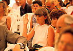 Newnham, Northamptonshire, England. A country house auction is conducted by the London auctioneers Christies at Newnham Hall. A young woman raises her hand to make a bid in the packed marques that has been set up in the ground of the hall for the auction. 1994r. 1990s UK