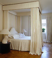 The four-poster bed in this romantic feminine bedroom is draped in white fabric
