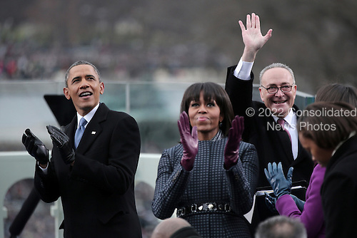 United States President Barack Obama, left, first lady Michelle Obama, center, and U.S. Senator Chuck Schumer (Democrat of New York) clap during the presidential inauguration on the West Front of the U.S. Capitol January 21, 2013 in Washington, DC.   Barack Obama was re-elected for a second term as President of the United States.      .Credit: Win McNamee / Pool via CNP