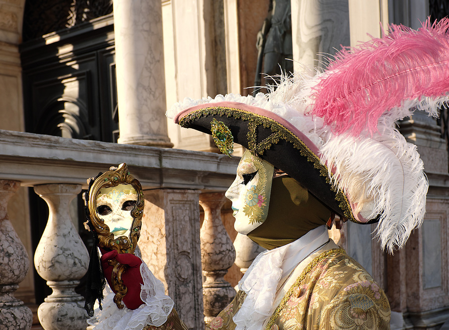 Man looking into mirror dressed in traditional mask and costume for Venice Carnival standing in Piazza San Marco, Venice, Veneto, Italy