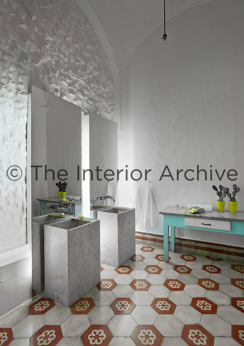 In the bathroom a pair of sinks made in veined marble are backed by contemporary mirrors and stand on an early 20th century concrete tiled floor