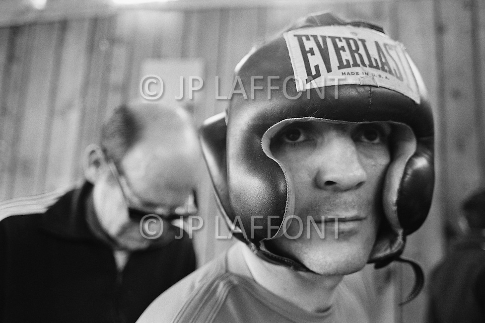 11 May 1970, Concord, New York State, USA. Marcel Cerdan Jr. wearing boxing headgear while training for his fight against Donato Paduano, which will be held at Madison Square Garden. His trainer Philippe Filippi stands behind him. Image by © JP Laffont