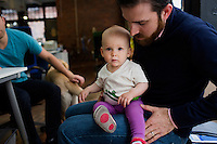 Mike Gutner (right), who handles operations at Mimo, his 10-month-old daughter Sadie Gutner as he speaks with Thomas Lipoma, Mimo co-founder and co-CTO, the Mimo headquarters Boston, Massachusetts, USA, on Mon., April 28, 2014. Sadie, daughter of Mike Gutner, is wearing one of the company's onesies, made by Mimo, which has a variety of sensors on it. The onesie has a detachable frog-shaped communication device that transmits data from the onesie's sensors and sends the data to a smartphone app, which displays information about the baby's respiration, skin temperature, position, and activity level. The onesie is washable and the device is water-resistant.