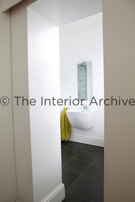 A view through an open doorway to a modern white bathroom with a grey tiled floor. The room has a wall-mounted washbasin with a mirror above.