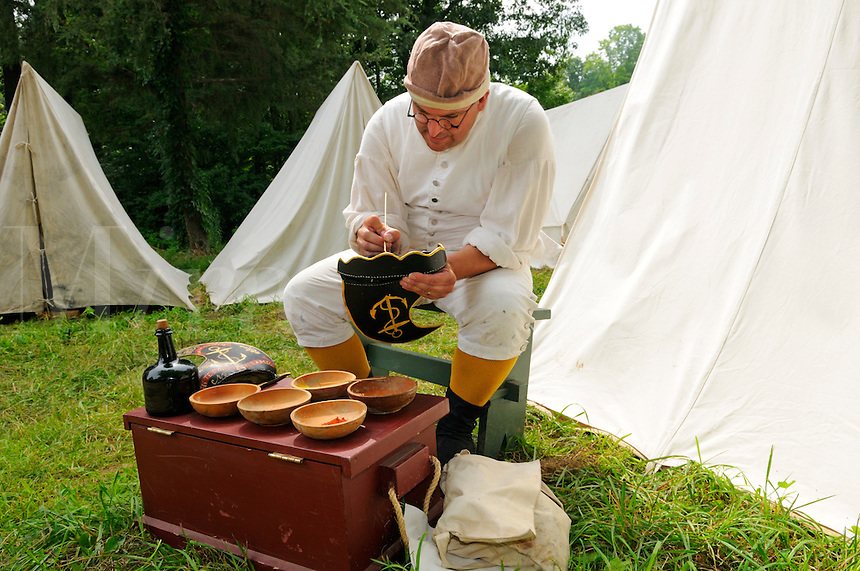 "Soldier of the United Train of Artillery from Rhode Island, paints a black leather, wave-crest shaped helmet with an anchor and motto ""For Our Country"" at a Revolutionary War encampment, Old Sturbridge Village, Massachusetts, USA."