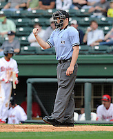 Umpire Andrew Freed signals an out in a game between the Charleston RiverDogs and Greenville Drive on Saturday, April 6, 2013, at Fluor Field at the West End in Greenville, South Carolina. Charleston won Game 1 of a doubleheader, 6-2. (Tom Priddy/Four Seam Images)