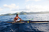FRENCH POLYNESIA, Tahaa Island. Roe, riding his outrigger canoe between Tahaa Island and Vahine Island. Tahaa Island can be seen in the background.