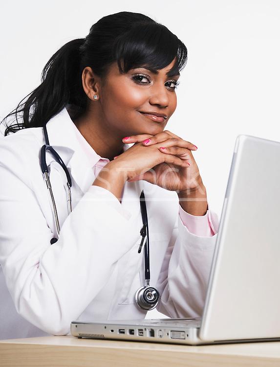 Female doctor using laptop, portrait