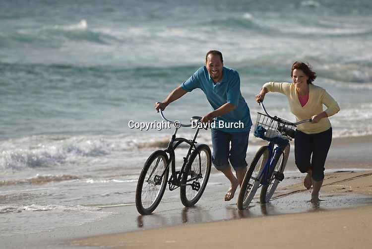 Mature couple running with bicycles at seashore, smiling