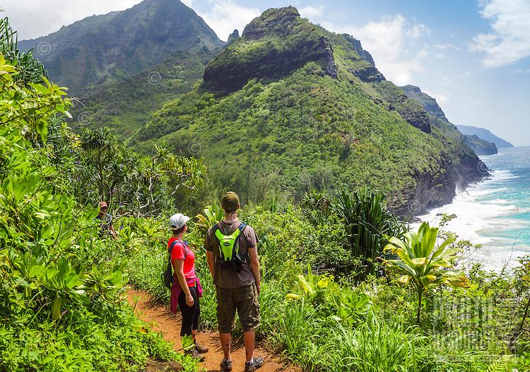 Two hikers admire the view along the Kalalau Trail near Hanakapi'ai Beach, Kaua'i.