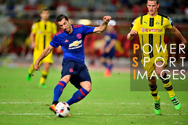 Manchester United midfielder Henrikh Mkhitaryan (l) attempts a kick while is observed by Borussia Dortmund midfielder Nuri Sahin (r) during the International Champions Cup China 2016, match between Manchester United vs Borussia  Dortmund on 22 July 2016 held at the Shanghai Stadium in Shanghai, China. Photo by Marcio Machado / Power Sport Images