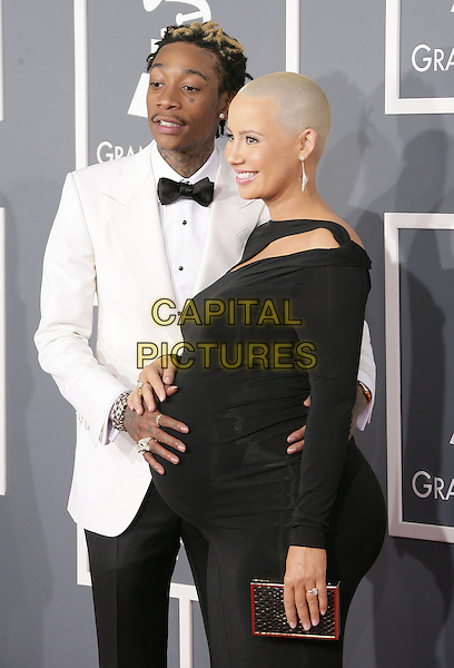 Wiz Khalifa & Amber Rose.The 55th Annual GRAMMY Awards held at STAPLES Center, Los Angeles, California, USA..February 10th, 2013.grammys half length black bow tie dress white tuxedo jacket side profile couple pregnant clutch bag.CAP/ADM.©AdMedia/Capital Pictures.