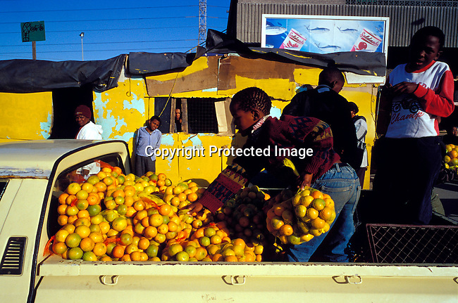 dibuven00096 .Small business. Boys selling oranges from a pick-up truck on July 25, 2001 in Site B Khayelitsha, a township about 35 kilometers outside Cape Town, South Africa. Khayelitsha is one of the poorest and fastest growing townships in South Africa. People usually come from the rural areas in Eastern Cape province to find work as maids and laborers. Most people don't find work and the unemployment rate is very high, together with lot of violence and a growing HIV-Aids epidemic itÕs a harsh area to live in..©Per-Anders Pettersson/iAfrika Photos.