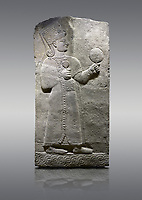 Picture &amp; image of Hittite relief sculpted orthostat stone panel of Long Wall Basalt, Karkamıs, (Kargamıs), Carchemish (Karkemish), 900-700 B.C. Anatolian Civilizations Museum, Ankara, Turkey.<br /> <br /> Goddess Kubaba. Goddess is depicted from the profile. The part below the chest of the relief is broken. She holds a pomegranate in her hands on her chest. She carries a one-horned headdress on her head. Her braided hair hangs down to her shoulder. The text in the hieroglyphics is not understood. The lower part of the relief has been restored. <br /> <br /> On a gray background.