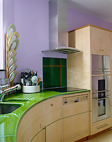 A modern kitchen with a curved green Pyrolave worksurface and purple walls.